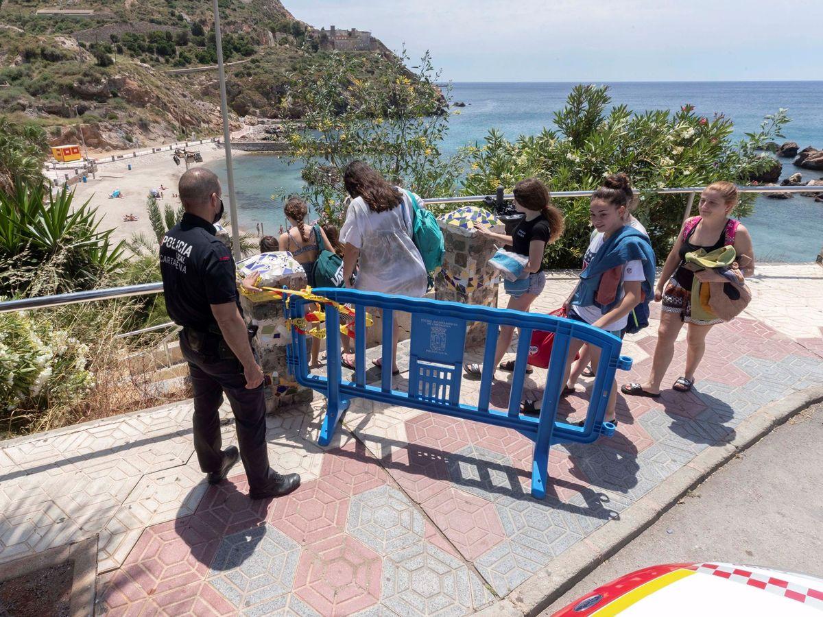 Foto: Un policía local controla el acceso de entrada a la playa de Cala Cortina en Cartagena, con un aforo de 28 personas durante el estado de alarma (EFE)