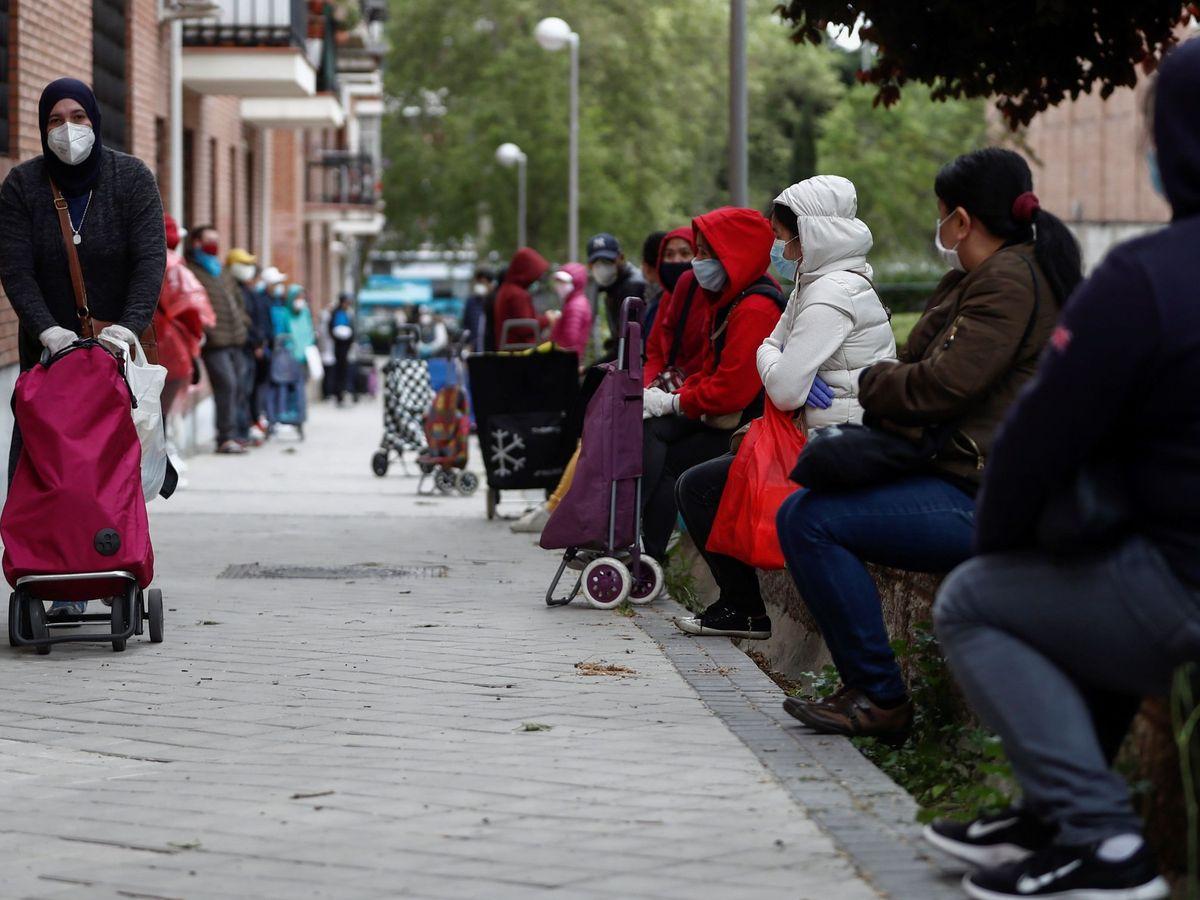 Foto: Personas hacen cola ante el Banco del Bebé de la Fundación Madrina, en la parroquia Santa María Micaela de Madrid, que diariamente reparte alimentos (EFE)
