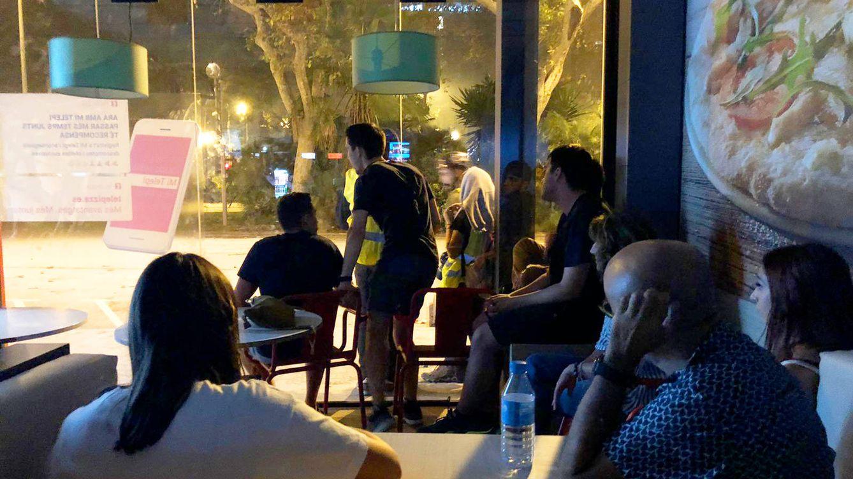 Foto: Atónitas, una decena de personas observan los disturbios desde el local de la pizzería. (A. V.)