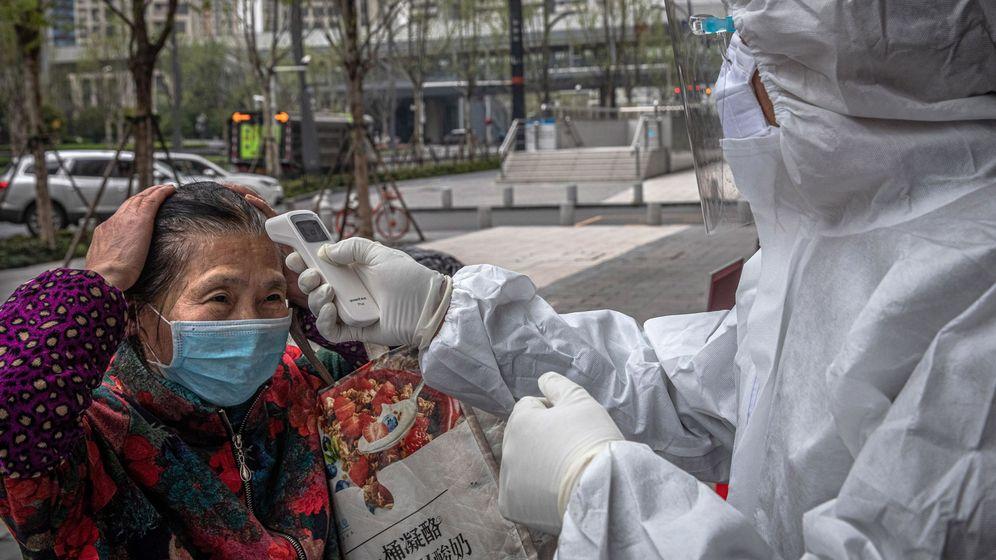Foto: Un trabajador comprueba la temperatura de una mujer en Wuhan. (EFE)