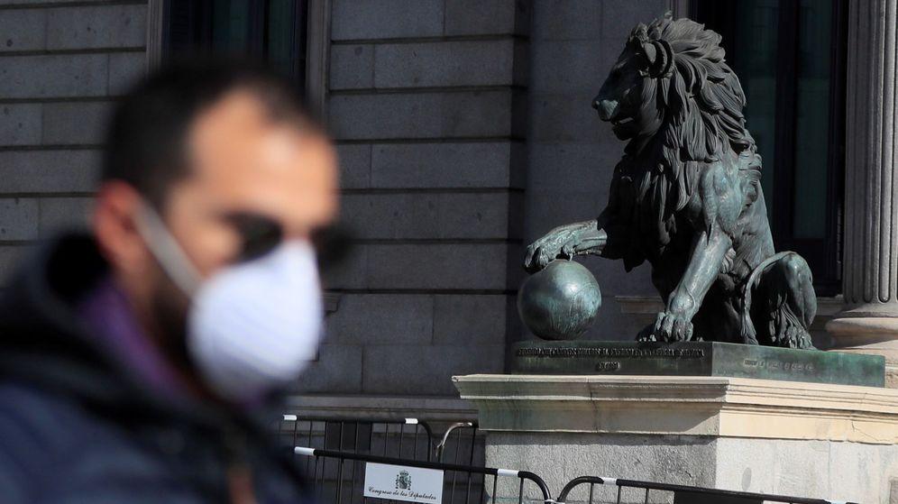 Foto: Un hombre con mascarilla pasea frente al Congreso de los Diputados en Madrid. (EFE)