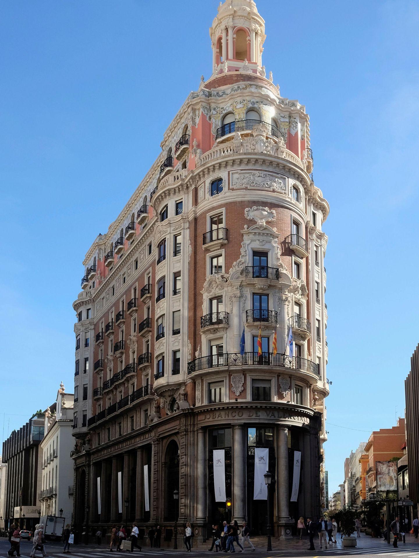 El edificio de CaixaBank, con las banderas de la UE, de España, de la Comunidad Valenciana y del banco.