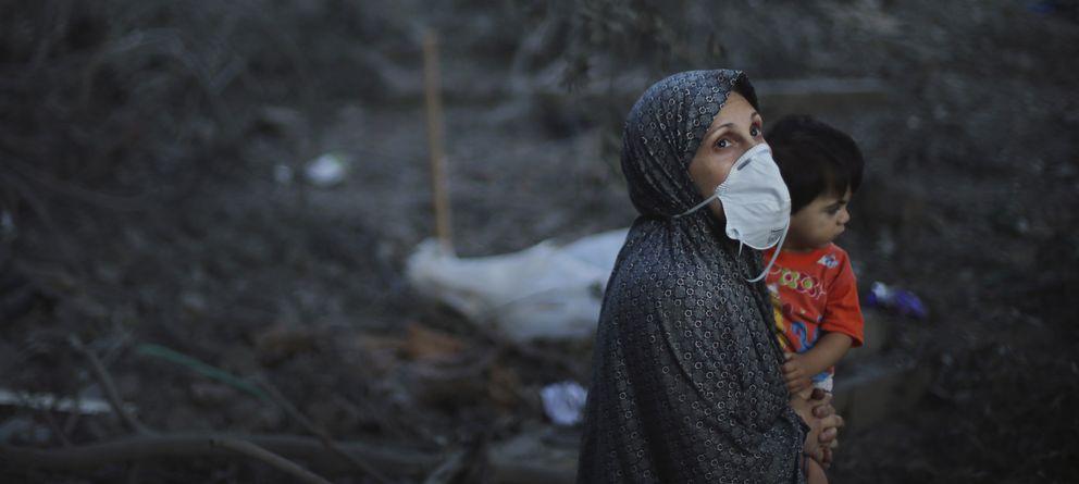 Foto: Una mujer palestina con su hijo pequeño observa el cielo ante los restos de su casa destruida en un bombardeo israelí contra Ciudad de Gaza (Reuters).