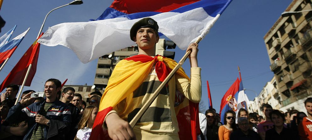 Foto: Un serbio cubierto con la bandera española durante una protesta de serbokosovares en la ciudad de Mitrovica, en Kosovo (Reuters).
