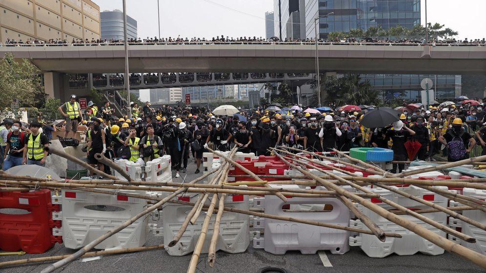 Foto: Varios manifestantes permanecen tras una barricada durante una marcha contra el Gobierno en Hong Kong (China). (EFE)