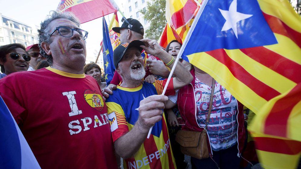 Foto: Un hombre con una bandera independentista (c), junto a otros con banderas españolas. (EFE)