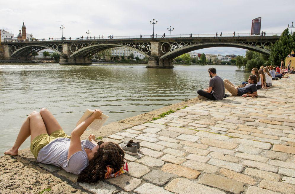 Foto: Sevillanos descansando junto al río Guadalquivir. (EFE)