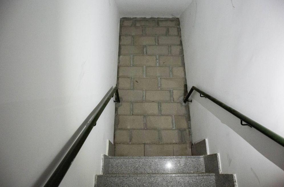 Foto: Un muro en mitad de una escalera comunitaria para aislar a okupas. (D. B.)
