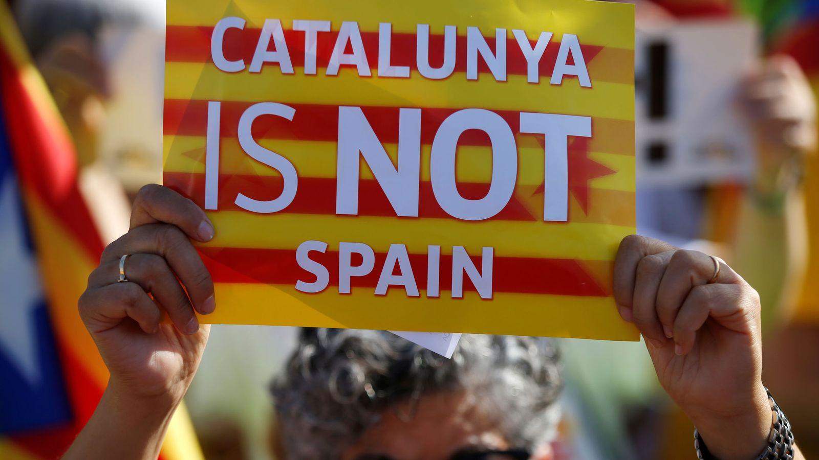 Foto: Una manifestante sostiene una pancarta con el lema 'Cataluña no es España'. (Reuters)