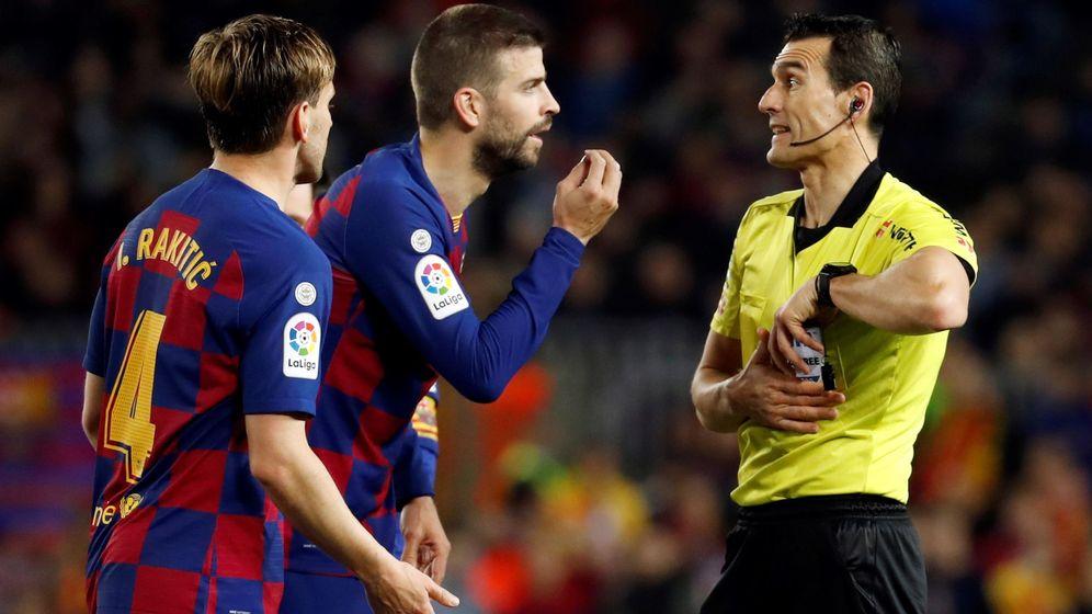 Foto: Gerard Piqué y Rakitic discuten con Juan Martínez Munera en un partido de Liga en el Camp Nou. (EFE)