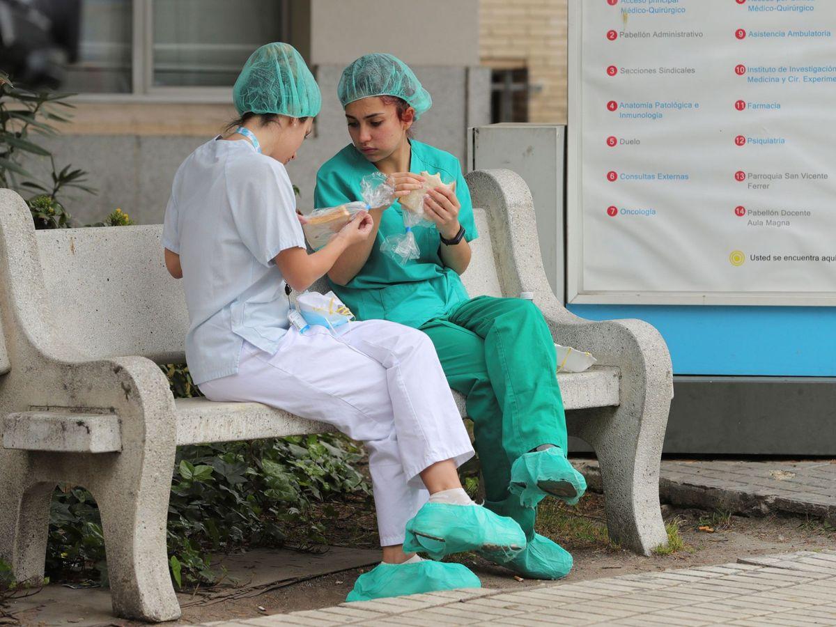 Foto: Dos sanitarias hacen un receso en la puerta de un hospital madrileño. (EFE)