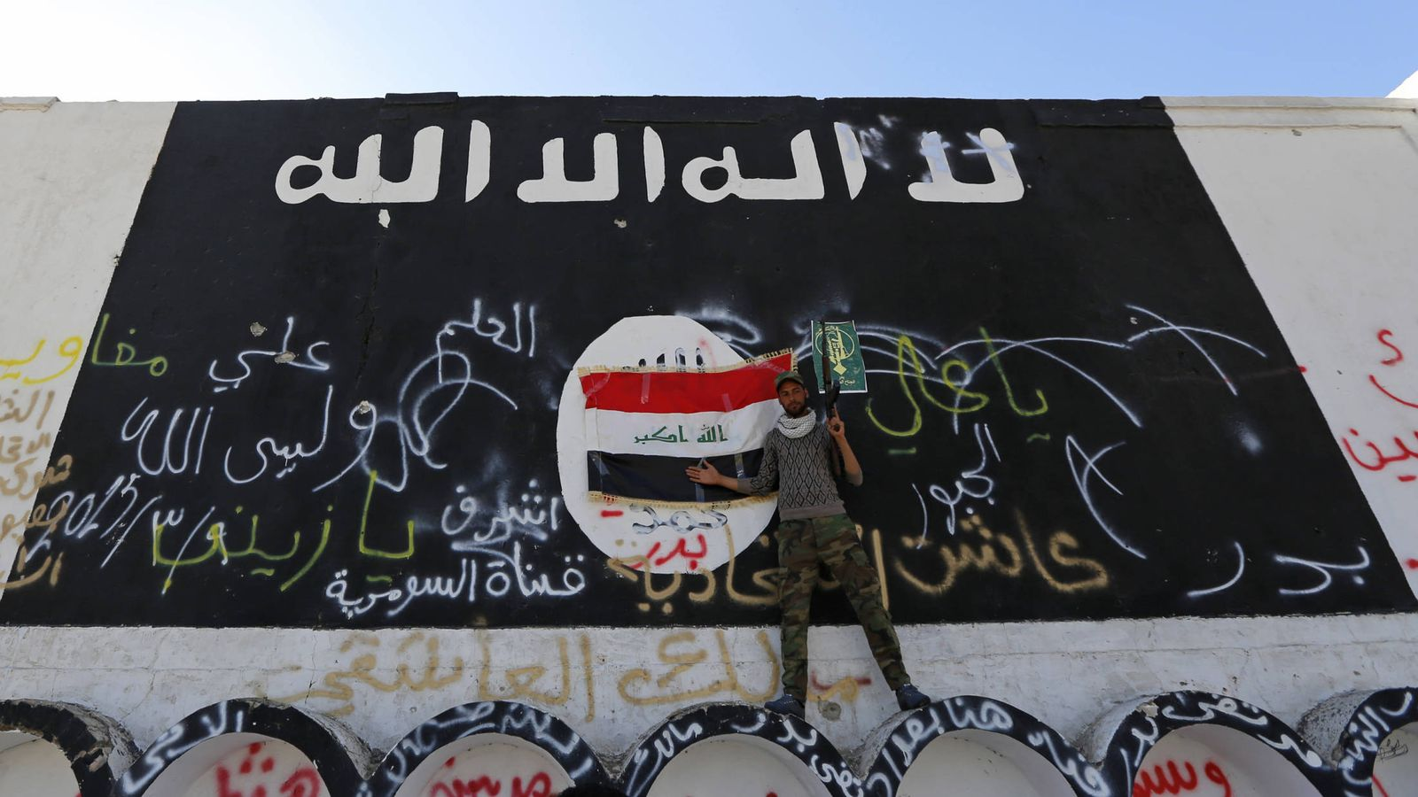 Foto: Un miliciano del Estado Islámico, ante una bandera de ISIS en Al-Alam (REUTERS)