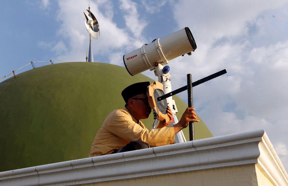 Foto: Un musulmán observa en qué fase se encuentra la luna desde una mezquita de Yakarta. (Reuters)