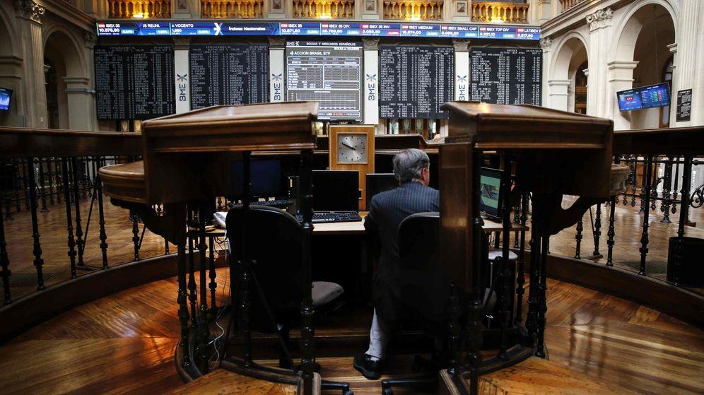 Foto: Un inversor sigue en el parqué madrileño la evolución del principal indicador de la bolsa española. (EFE)