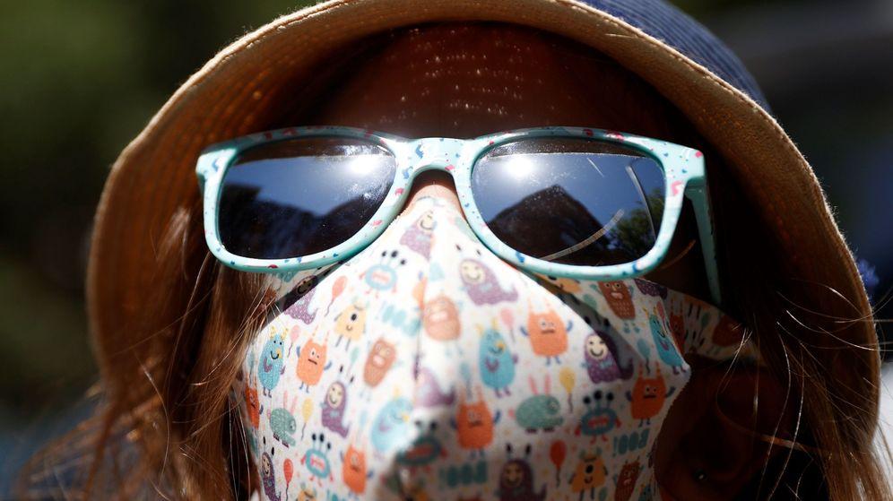 Foto: Una niña se protege del sol con sombrero y gafas. (EFE)