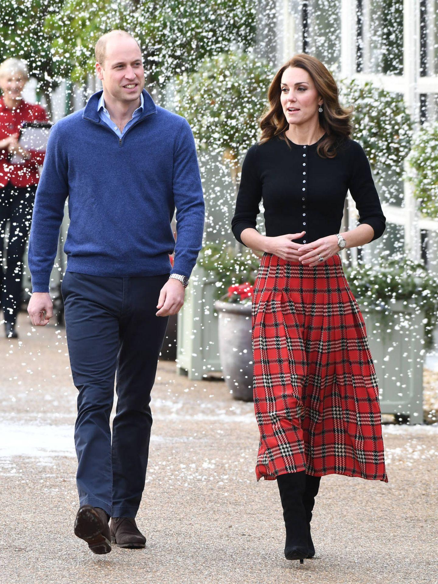 Kate Middleton, con falda plisada de tablas y estampado tartán junto al príncipe Guillermo. (Getty)