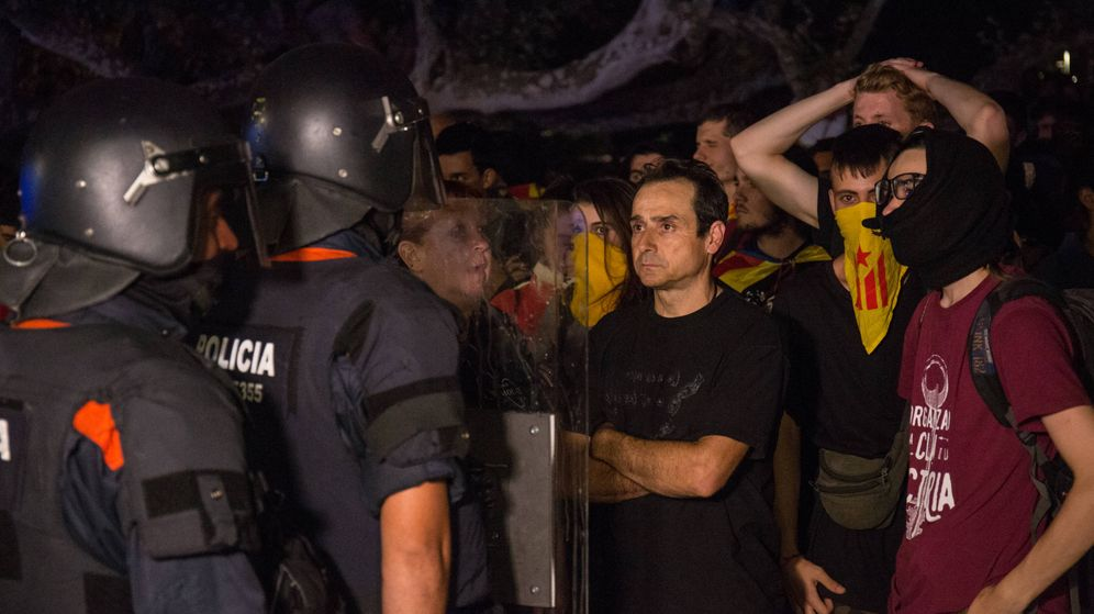 Foto: Un hombre se encara a un agente antidisturbios de los Mossos d'Esquadra frente al Parlament. (David Brunat)