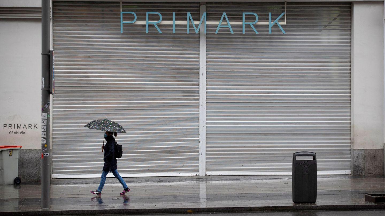 Una mujer pasa ante una tienda de ropa ubicada en la Gran Vía de Madrid durante el estado de alarma. (EFE)