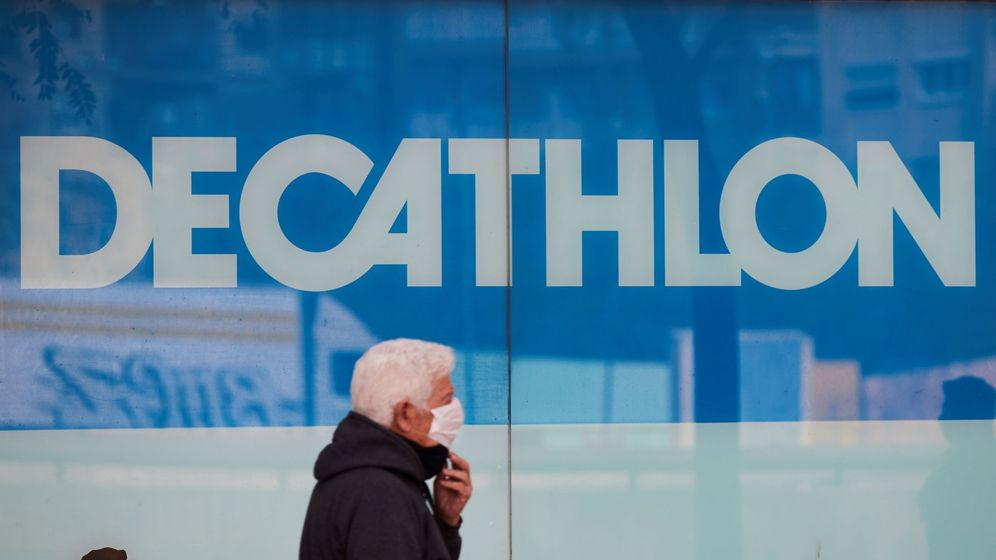 Foto: Un hombre con mascarilla pasa junto a una tienda de Decathlon en Barcelona (EFE)