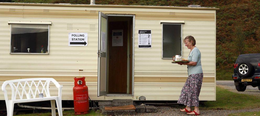 Foto: Una mujer lleva una tetera a un colegio electoral en los Highlands (Reuters)