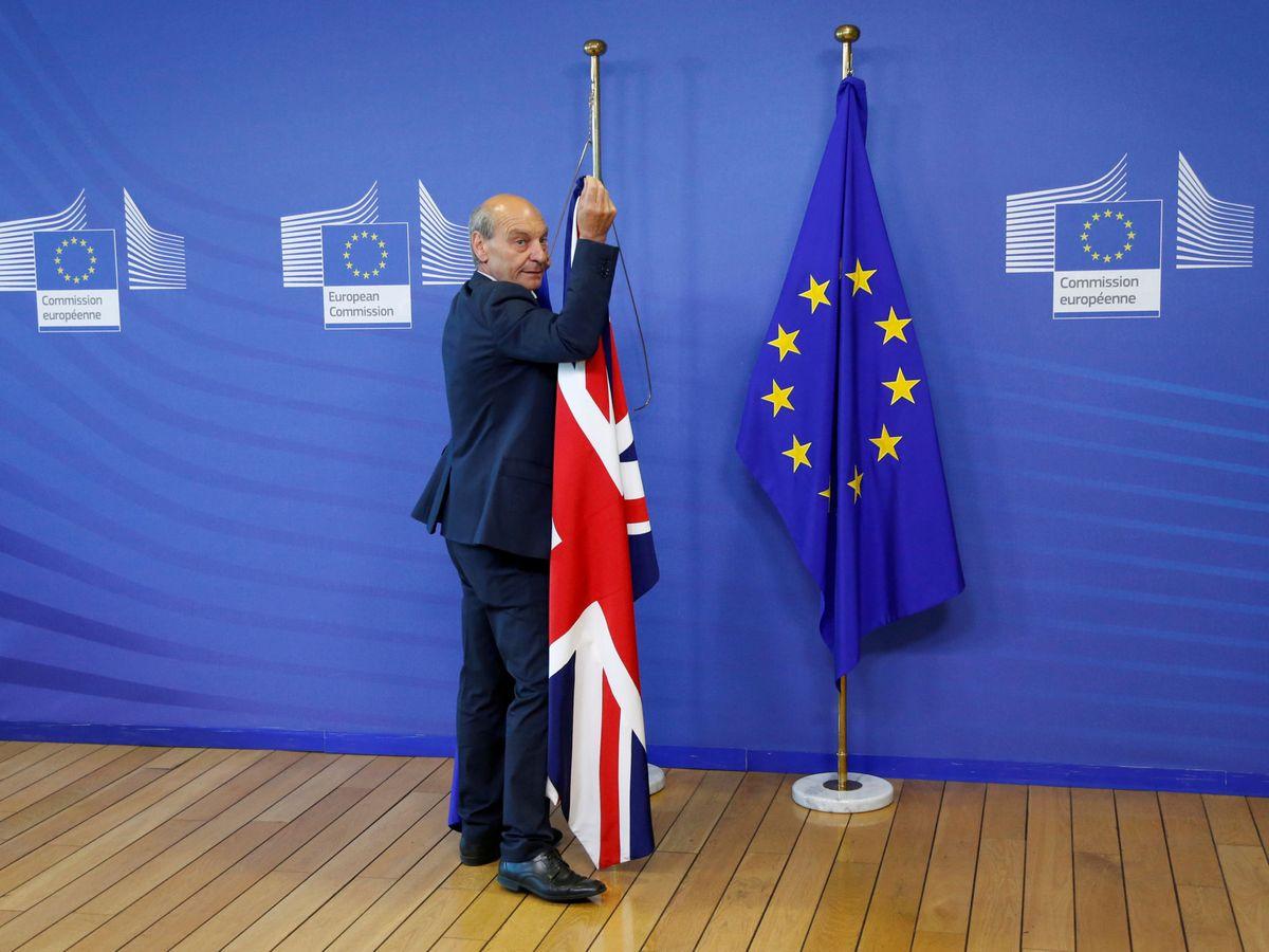 Foto: Un trabajador de la Comisión Europea retira la bandera británica. (Reuters)