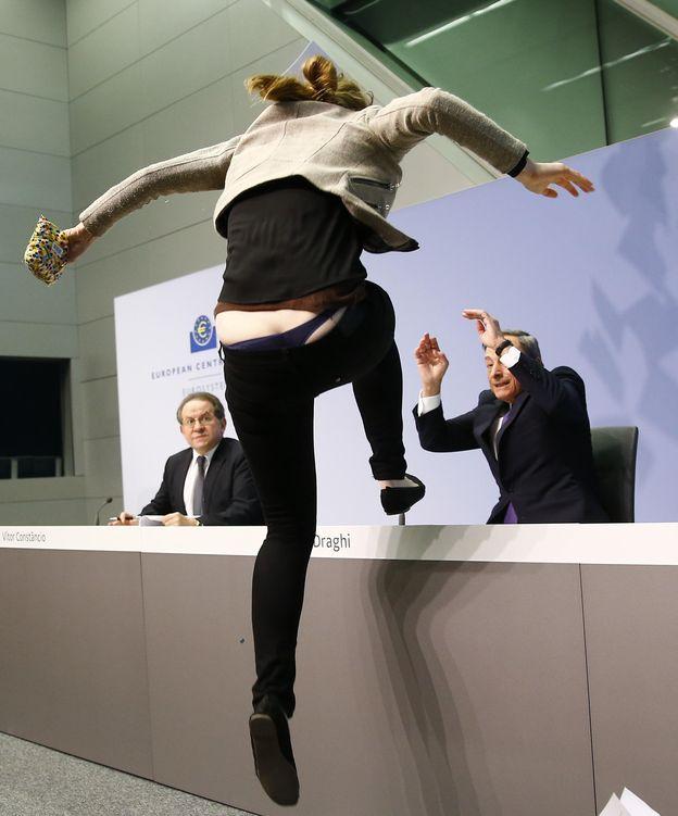 Foto: La activista saltando sobre la mesa de una sola zancada mientras Draghi se protege como puede (REUTERS)