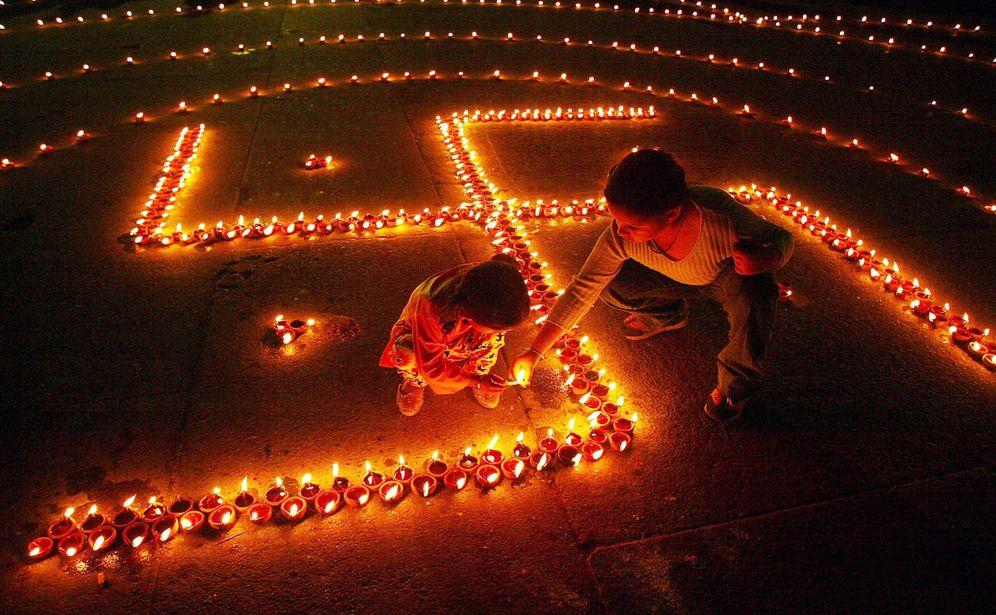 Foto: Dos niños encienden lámparas que conforman una esvástica en la festividad hindú de Diwali, en la ciudad de Chandigarh, India, en 2004. (Reuters)