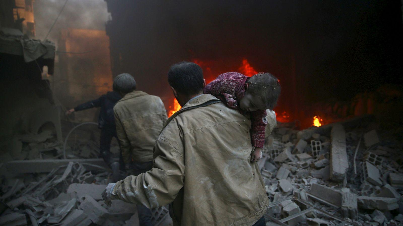 Foto: Un hombre rescata a un nño entre los escombros tras un ataque aéreo del régimen en Duma (Reuters).