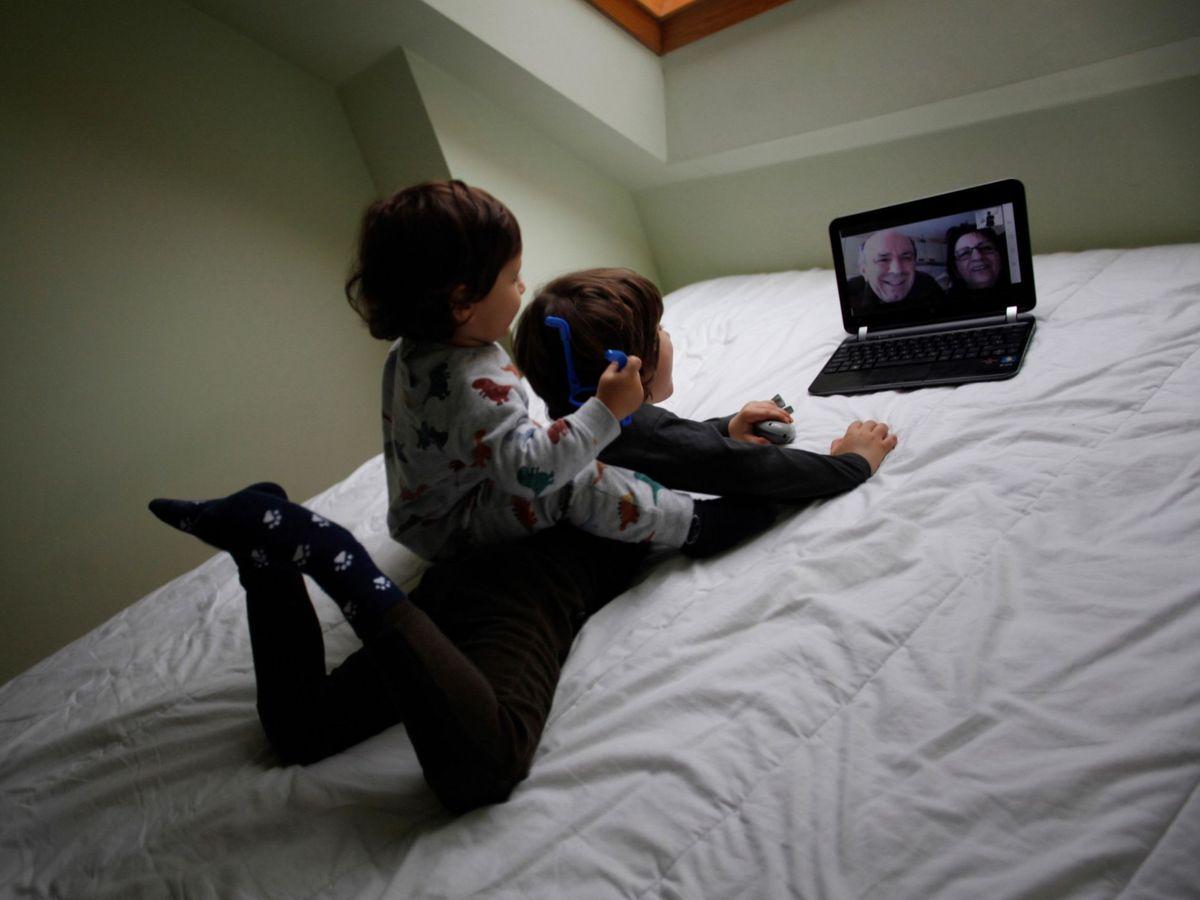 Foto: Dos niños conversan con sus abuelos por medio de una videollamada (EFE)