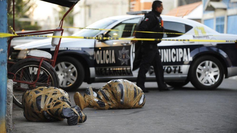 Foto: Un oficial de policía cerca de los cadáveres de dos personas asesinadas en Nezahualcoyotl, México (Reuters)