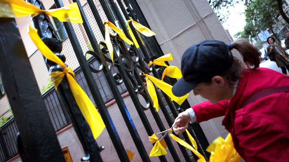 Foto: Ciudadanos contrarios a la independencia retiran lazos amarrillos en Barcelona. (EFE)