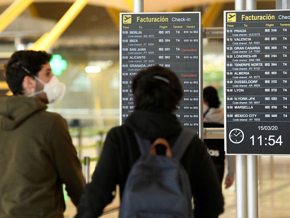 Foto: Dos pasajeros se protegen con mascarillas, el pasado día 15 en el Aeropuerto Adolfo Suarez Madrid Barajas. (EFE)