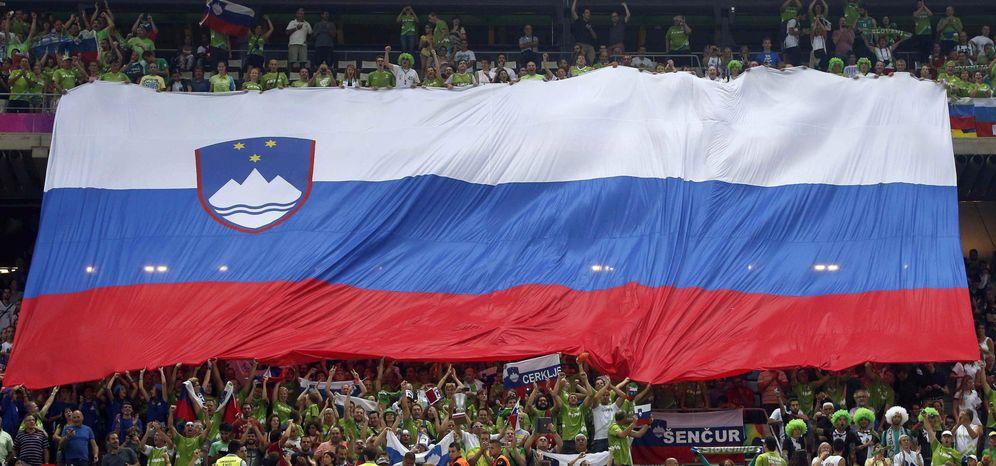 Foto: Aficionados de Eslovenia muestran su bandera durante un partido de baloncesto. (EFE)