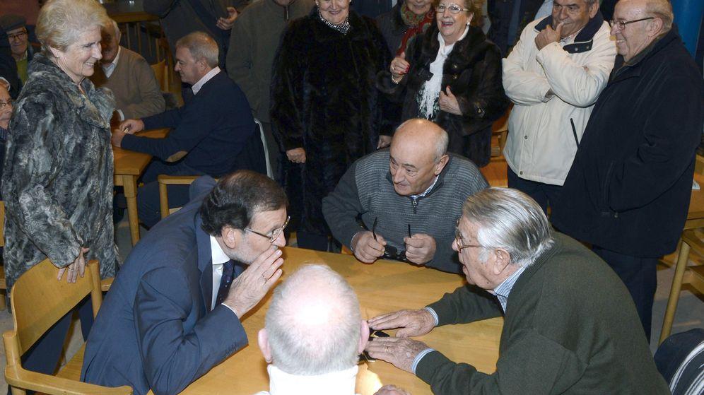 Foto: Mariano Rajoy (i), conversa con su pareja de juego momentos antes de disputar una partida de dominó en el Hogar del Pensionista, tras su intervención en un mitin en Olmedo en 2015. (EFE)