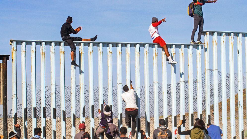 Foto: Integrantes de la caravana de centroamericanos escalan el muro fronterizo en Tijuana. (EFE)