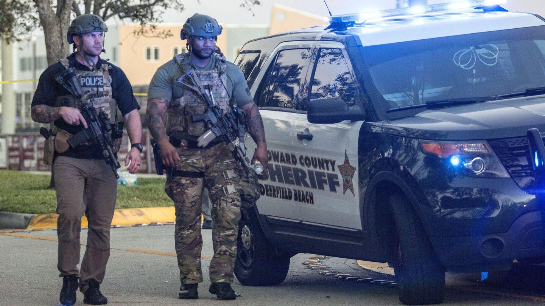 Dos miembros del equipo SWAT montan guardia frente a la entrada lateral tras el tiroteo. (EFE)