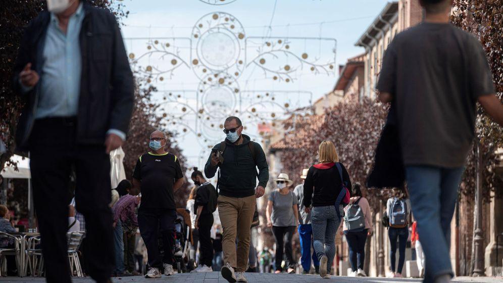 Foto: Gente paseando por la calle con mascarilla. (EFE)