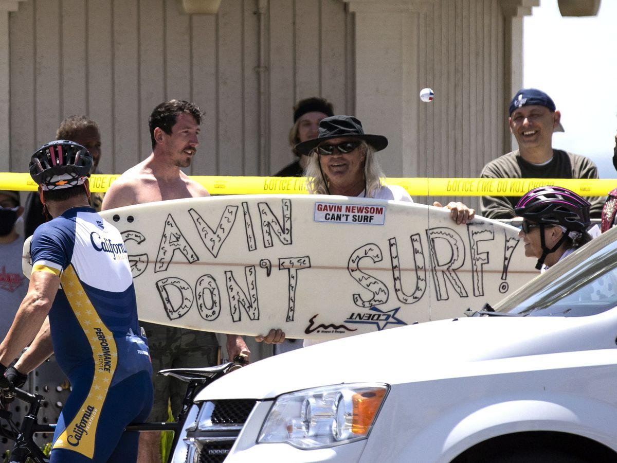 Foto: Una manifestante pide que se cierren las playas en California. (EFE)