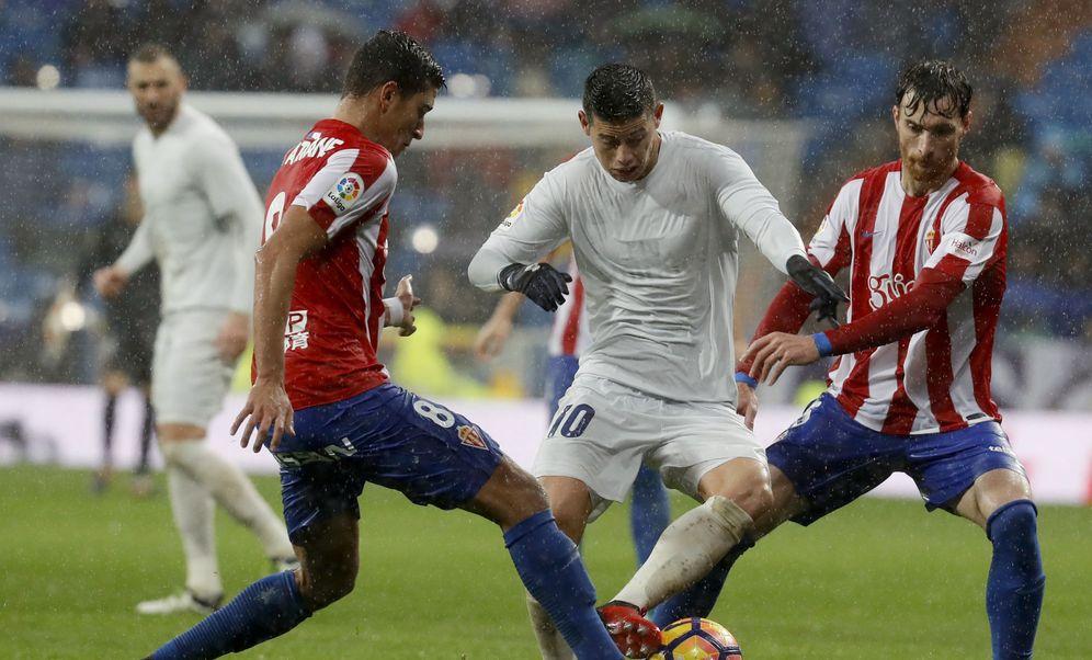 Foto: James Rodríguez, entre dos jugadores del Sporting, volvió a sellar un más que discreto partido (EFE)