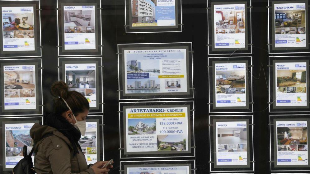 Foto: Una mujer pasa por delante de un portal inmobiliario de venta y alquiler. (EFE)