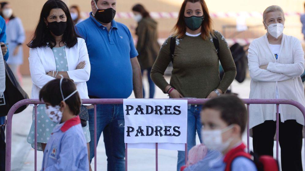 Foto: Un grupo de padres observa la entrada de sus hijos en un colegio de Valladolid. (EFE)