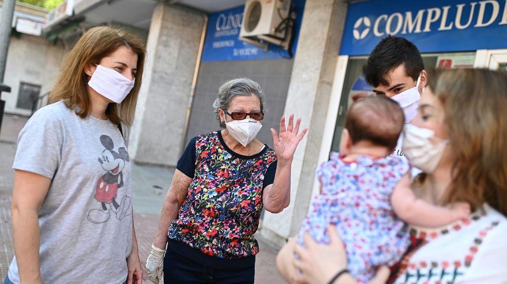 Foto: Un grupo de personas se saludan en la calle portando mascarillas. (EFE)