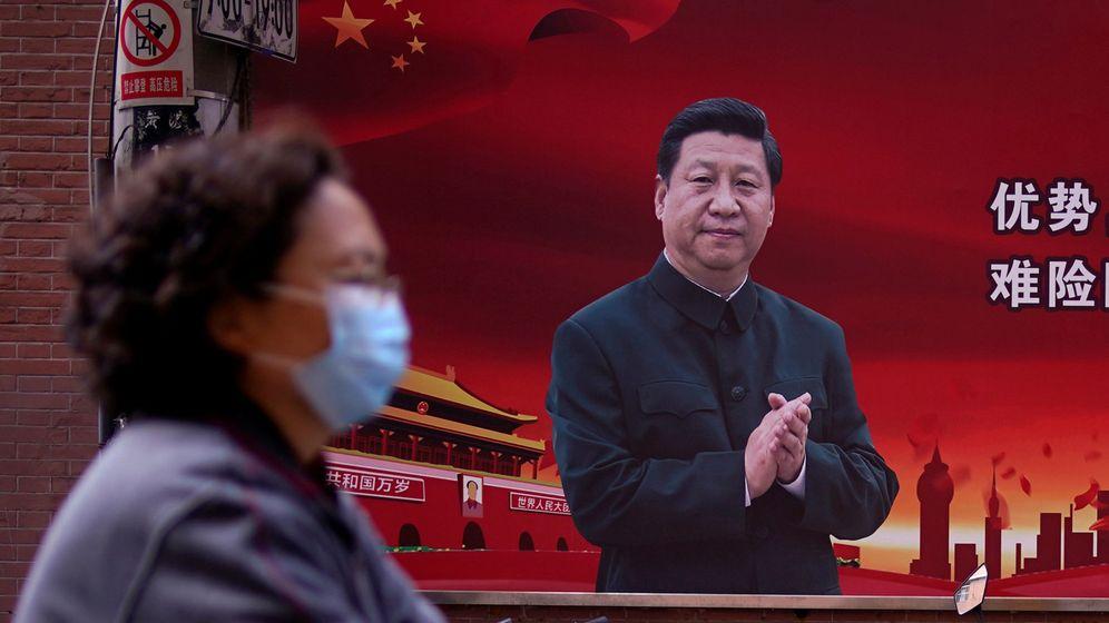 Foto: Una mujer con mascarilla y, detrás, propaganda china con la imagen de Xi Jinping, en Shanghái. (Reuters)