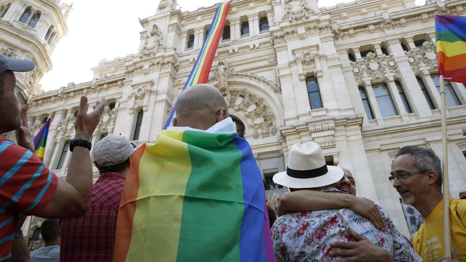 Foto: Un hombre con la bandera LGTB, enfrente del Ayuntamiento de Madrid. (EFE)