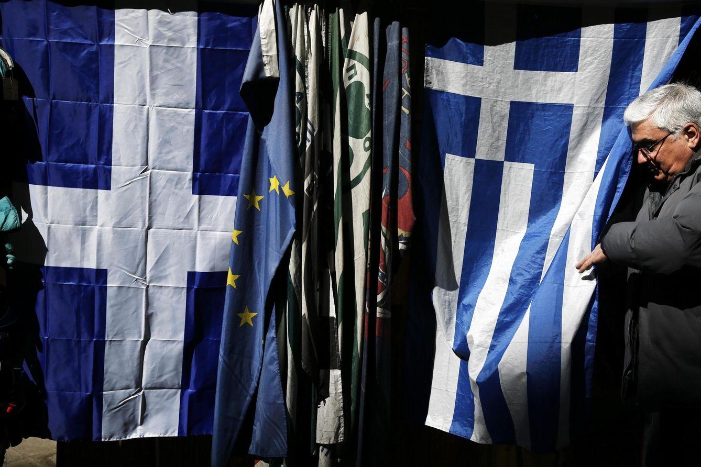 Foto: El dueño de un quiosco del centro de Atenas aparece tras una bandera griega. (Reuters)