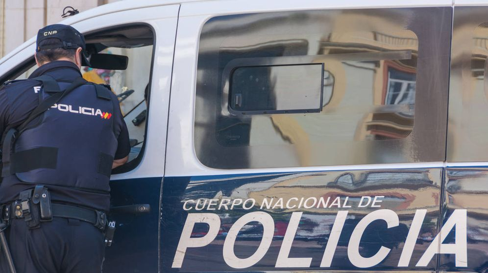 Foto: Agentes junto a un coche patrulla de la Policía Nacional (iStock)