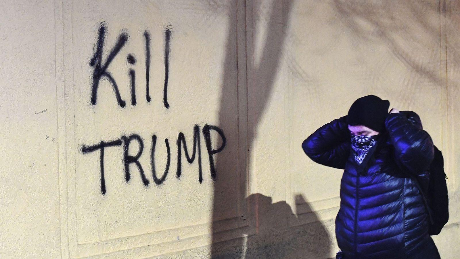 Foto: Una mujer camina junto a una pintada que reza 'Matad a Trump'. (EFE)