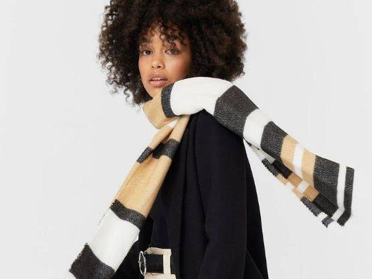 Foto: Combina tu abrigo negro de siempre con esta bufanda de rayas de Stradivarius. (Cortesía)