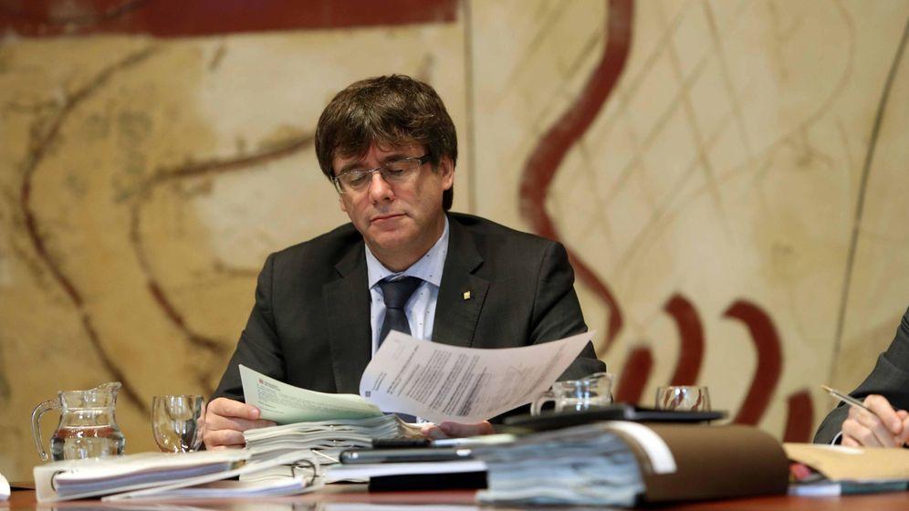Foto: El presidente de la Generalitat, Carles Puigdemont, repasa unos papeles durante una reunión del Govern. (EFE)