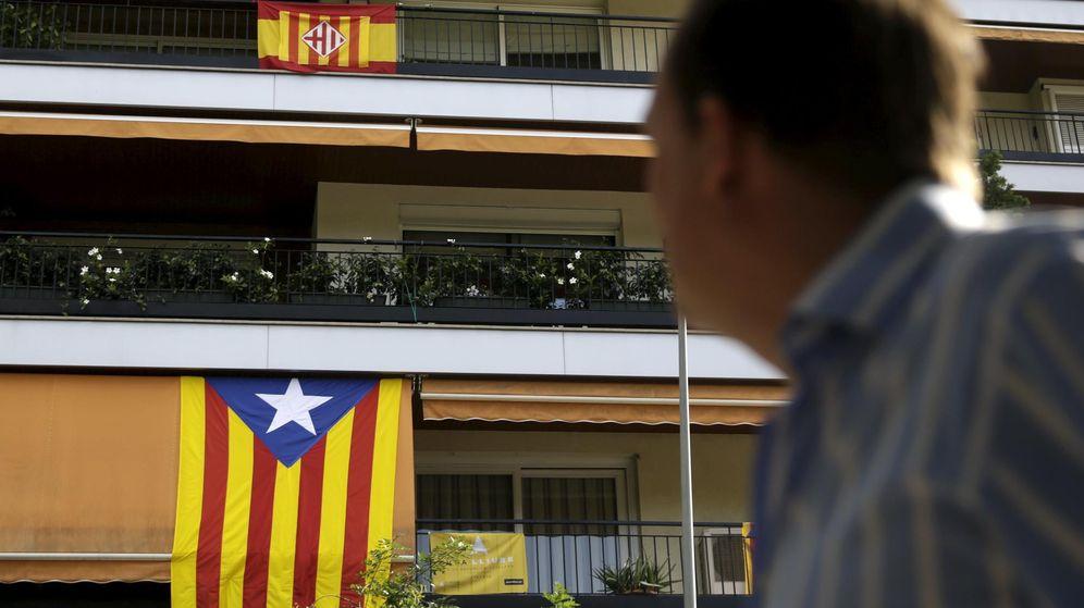 Foto: Un hombre mira la bandera española y una estelada colgadas de una fachada. (Reuters)